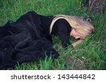 Sad blond woman in black dress lying on the grass - stock photo