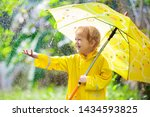 Child Playing In The Rain On...