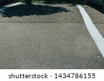 Small photo of Empty parking lot on grey asphalt with white delimitation lines outdoor with copy space – One vacant car park in the city on a rough concrete surface