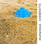 Small photo of Closeup of toy pyramid on the beach. Blue plaything lies on the sand. Shallow depth of field, soft focus, selective focus.