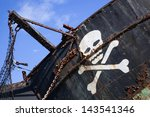 Small photo of white skull with crossed bones on a rusty old black pirate ship