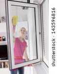 Housewife with protective glove washing the window glass. - stock photo