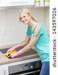 Beautiful housewife cleaning in the kitchen. - stock photo