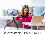 Young female blogger on camera screen. Young woman recording her daily video blog on a tripod mounted camera. Young woman looking at camera while working on laptop.