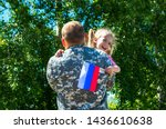 Happy reunion of soldier from Russia with family, daughter hug father. A little girl holds the flag of Russia in her hand