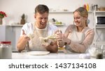 Small photo of Carefree couple clumsily kneading dough, having fun in kitchen, inept chefs