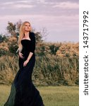 Outdoors portrait of a blond woman in long black dress at sunset - stock photo
