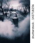 Woman in black standing in the fog, monochromatic shot - stock photo