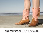 girl standing on beach wearing cowboy boots - stock photo
