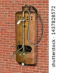 Small photo of Vintage gas water heater with shower on wall of bricks. Retro Instantaneous water heater with tap.