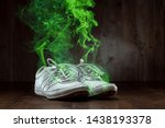 Small photo of White sneakers closeup on a wooden background, stink. Nasty smell. Stink legs, fungus on the legs.