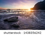 Small photo of Tropical beach in ebb time low tide on sunset. Mudflats and sun reflections at the golden hour. mountain chain isles at horizon. Coron Corong beach, El Nido, Phillipines