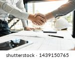 Small photo of Architect and engineer construction workers shaking hands while working for teamwork and cooperation concept after finish an agreement in the office construction site, success collaboration concept