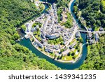 Aerial view of Esch-sur-Sure, medieval town in Luxembourg, dominated by castle, canton Wiltz in Diekirch. Forests of Upper-Sure Nature Park, meander of winding river Sauer, near Upper Sauer Lake.