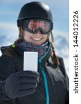 Small photo of Winter sport girl with blank lift pass card smiling at camera. Concept to illustrate ski admission fee