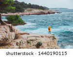 Small photo of woman in yellow raincoat with backpack standing on the cliff looking at inspirited sea