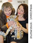 Small photo of MOSCOW - OCT 22: Circus actress, animal trainer Karina Bagdasarova with tiger cub and soviet and russian musician and producer Bari Alibasov at Phoney New Year celebration, Oct 22 2012, Moscow Russia.