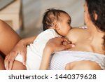 Small photo of Close-up of young black mother attaching baby at breast while giving nipple to son during breastfeeding