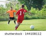 Boy Kicking A Ball At Goal