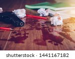 Stock photo gun with red flesh blood over pencils with books and crumpled paper ball tile concrete floor 1441167182