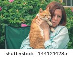 Stock photo a young woman sits on a chair and holds a red cat in her arms and hugs him sad face pain and 1441214285