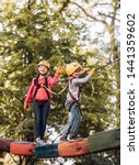 Small photo of Child playing on the playground. Balance beam and rope bridges. Go Ape Adventure. Hiking in the rope park girl in safety equipment. Adventure climbing high wire park. Child concept