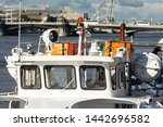 Small photo of A closeup of an empty white tentbooth outside. ship's rescue and signaling equipment. in the background is a bridge over the river and cranes in the dock. Russian text: throw overboard, pull the rope
