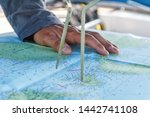Small photo of Sailor with divider in front of navigation chart of coastal area. Captain navigating sail boat ship