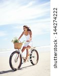 Woman Riding Bicycle On Beach...