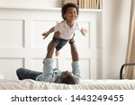 Small photo of Loving african American dad lying on bed playing with cute little toddler son acting plane, happy black father have fun engaged in funny activity with small kid hold lift in arms in bedroom