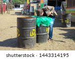 Small photo of Glastonbury, England - June 30 2019 - A man bends over to rummage through a painted rubbish bin at Glastonbury Festival 2019.