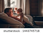 Small photo of Grandmother is making funny faces to newborn her grand daughter