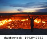 Silhouette of woman standing next to Darvaza Crater (Gateway to Hell) fire pit in Turkmenistan at sunrise