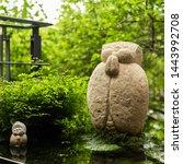 rough stone statue of Earth Store Bodhisattva(kṣitigarbha bodhisattva) near a pond