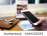 Small photo of Hands use the phone to scan QR codes to accumulate points in restaurants.