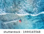 Aerial view of a young woman swimming with the pink donut swim ring in clear blue sea with beautiful waves at sunny day in summer. Tropical aerial landscape with girl, azure water. Top view. Travel