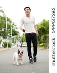 Stock photo vertical image of a smiling young man walking his pet 144437362