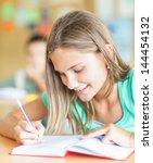 a cute schoolgirl writing... | Shutterstock . vector #144454132
