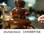 Small photo of Homemade chocolate fountain fondue with marshmallow on a skewer dripping in chocolate sauce on blurred background and copy space.