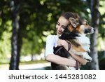 Stock photo welsh corgi pembroke dog and smiling happy woman together in a park outdoors young female in white 1445281082