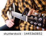 Small photo of Instal a capodaster, also called capo, for guitar, put across the strings. Closeup