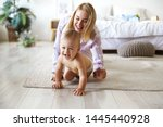 Cute cheerful European infant in diaper having joyful facial expression, laughing while crawling on floor from his smiling mother who is chasing him. Blonde young woman playing with son indoors