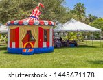 Vintage colorful small gazebo bounce house inflated next to a tent selling souvenirs for all who visit the festival. The sunny open tropical field is the perfect spot for community people to enjoy. - stock photo
