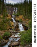 Small photo of Waterfall surrounded by nature and wildlife. Rocky mountain ( Canadian Rockies ). Near the city of Calgary. Portrait, fine art. Jasper, Yoho and Banff National Park, Alberta, Canada: August 4, 2018