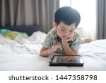 A Boy Using Tablet In The Room