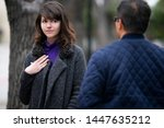 Small photo of Woman walking outdoors in the city and looking snobby while running into an ex boyfriend or looking annoyed by an insulting stranger. It also depicts social anxiety.