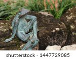 Statue Of Frog Resting On A Rock