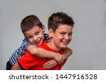 joyful older brother giving... | Shutterstock . vector #1447916528