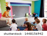 female teacher reading story to ... | Shutterstock . vector #1448156942