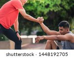 Small photo of Helping hand outstretched for salvation . Strong hold. Running man helping his friend. Man help each other to run on the running track.